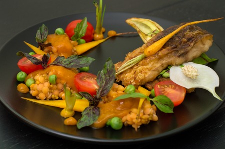 Dish from fried fish with lentils, green peas, apricot sauce, baby carrots and cherry tomatoes. Black wooden background. Top view. Close-up Stock Photo