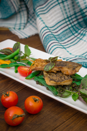 Fried fish with pea pods and cherry tomatoes. Wooden background. Close-up. Top view Stock Photo