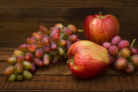 Apples and grapes on a wooden rustic background. Still life for thanksgiving with autumn fruits. Selective focus. Top view