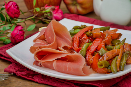 Jamon with grilled vegetables. Spanish cuisine. Wooden rustic background. Top view. Selective focus Stock Photo