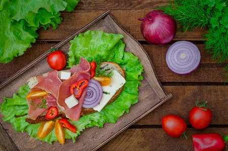 Ciabatta sandwich with salad leaves, jamon serrano and mozzarella. Wooden rustic background. Top view. Selective focus Stock Photo