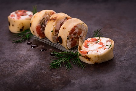 Rolls of thin pancakes with salmon, horseradish cream cheese. Black old background. Top view. Selective focus