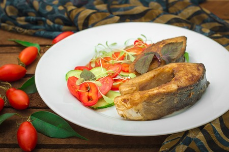 Grilled fish steak with vegetables on plate: tomatoes, microgran, cucumber, tasty and healthy dinner. Wooden rustic background. Top view.