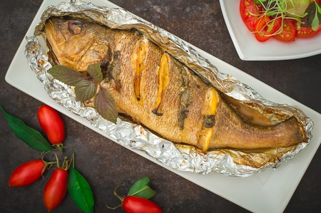 Fried fish with fresh tomatoes, herbs and lemon. Old black background. Top View.