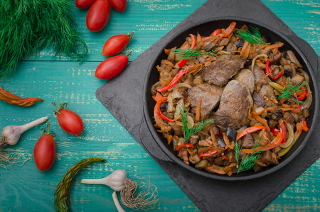 Fried chicken liver with vegetables and herbs in the frying pan. Wooden turquoise background. Top view. Stock Photo