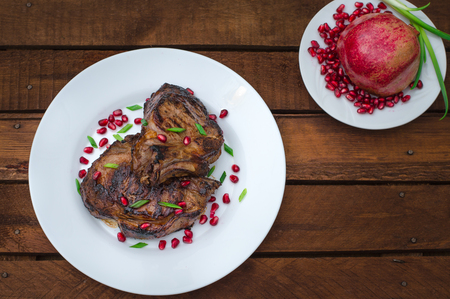Steak on ribs, cooked on a grill with pomegranate on a white plate. Wooden rustic background. Top view.