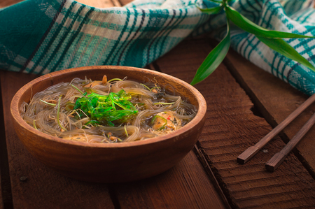 Japanese cuisine, soup with chashu pork, chives, sprouts, noodles and seaweed on the table under the sunlight. Wooden rustic background. Top view.