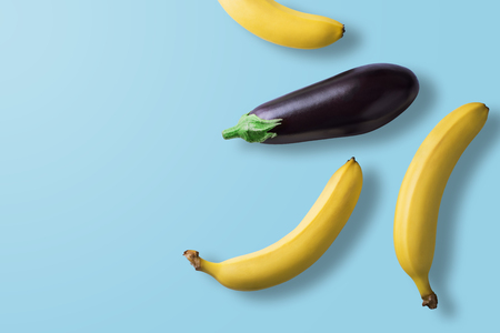 Bananas and eggplant on pastel blue background. Minimal fashion. Albino Different Creativity Creative Thinking Ideas Concept. Free space for text.