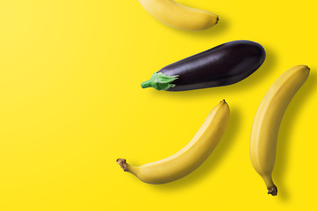 Bananas and eggplant on pastel yellow background. Minimal fashion. Albino Different Creativity Creative Thinking Ideas Concept. Free space for text