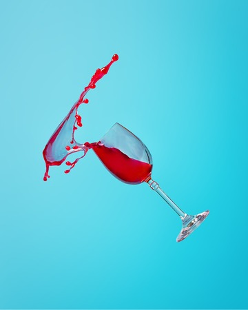 Abstract splash of red wine in a glass on a blue background close up Stock Photo