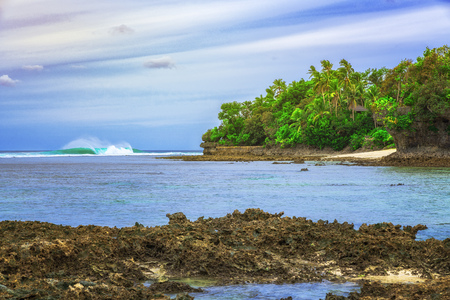 Clear blue water with corals and beautiful sky at beach for surfers Cloud, Siargao Island, the Philippines.