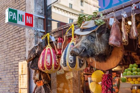Rome, Italy - November 11, 2018: Counter of the Minimarket in Rome, Italy with fruits, meats. Exterior decor in the form of a stuffed boar Редакционное