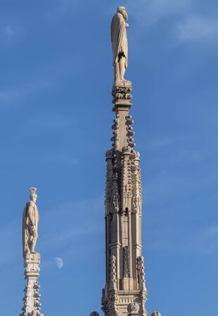 Milan Italy. Statues on the spires of the Duomo cathedral and moon
