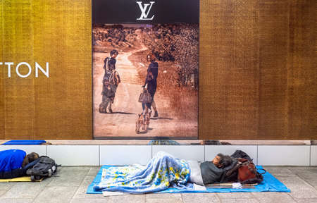 Tokyo Japan. A homeless spending night close to a luxury fashion shop in Shinjuku district Editorial