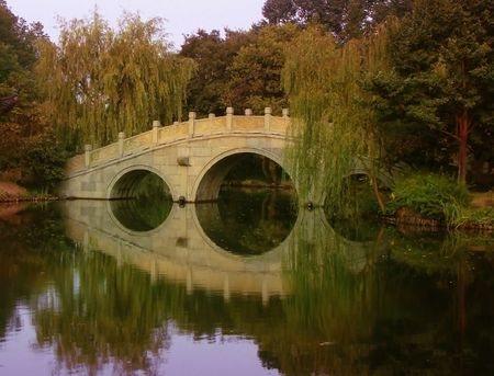 poetic: Ancient stone bridge, sky and trees reflecting in the waters of a West Lake park in Hangzhou China
