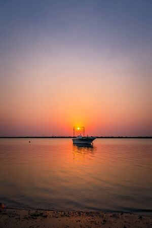 Beautiful Sunrise Boat in seaside with red and dark sky. Dammam -Saudi Arabia
