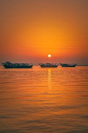 Beautiful Sunrise Boat in seaside with yellow sky. Dammam -Saudi Arabia Stock Photo