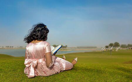 Reading Book at Dammam Modon lake Saudi Arabia enjoying winter season greenery blue sky background Banco de Imagens