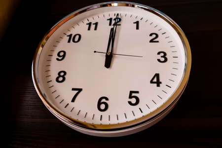 a top view of round white wall clock isolated on wooden table