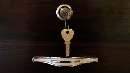 a close view of chrome handle with key lock isolated on wooden background