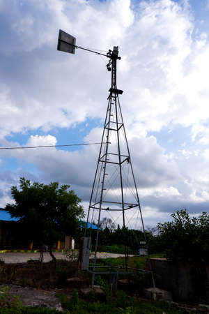 a long view of weather vane metal tower isolated in outdoor
