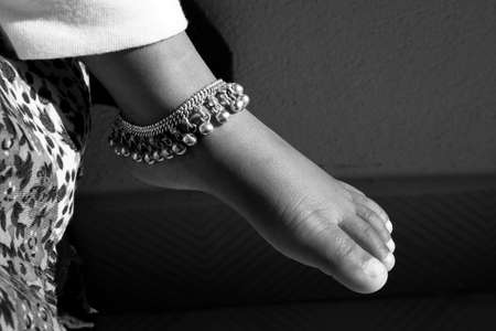 a closeup shot of Indian girl child ankle bracelet isolated on bare feet in black & white photo