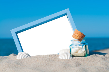 Blank picture frame in the sand with maritime decoration