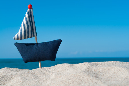 Sailing trip; Handmade Sailboat on sandy beach at clear blue sky; Maritim greeting card