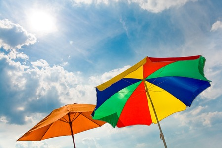 Colorful sun umbrellas in sunlight against partly cloudy sky