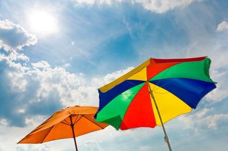 insolación: Sombrillas de colores en la luz del sol contra el cielo parcialmente nublado