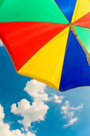 insolaci�n: Primer plano de parasol en los colores primarios en el cielo azul con nubes