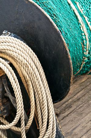 coiled rope: Green fishing net on a winch and coiled rope in enlarged detail Stock Photo