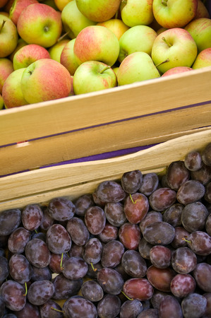 subsist: Juicy apples and plums in wooden fruit crates in close-up