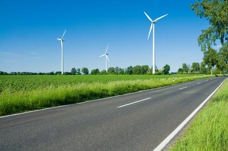 Wind turbines against blue sky in green landscape beside a road; Alternative energy
