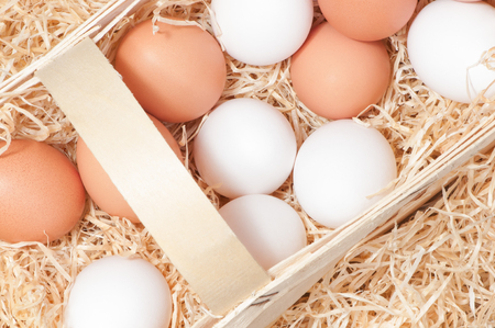 wood chip: White and brown chicken eggs in wooden basket with wood chip wool