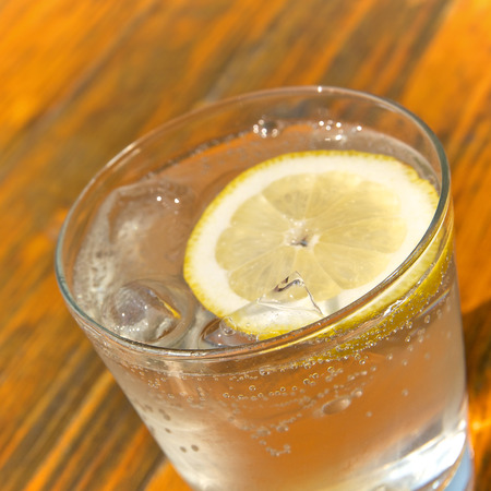 thirst quenching: Glass of sparkling water with ice cubes and a slice of lemon; Thirst quencher