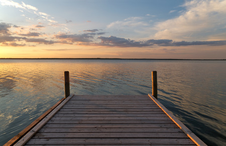 atmospheric: Enjoy the silence; Wooden jetty on lake shore with atmospheric sundown; The end of the way Stock Photo