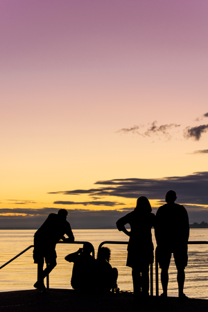 closing time: Black silhouette of people watching a wonderful sundown; Special evening atmosphere