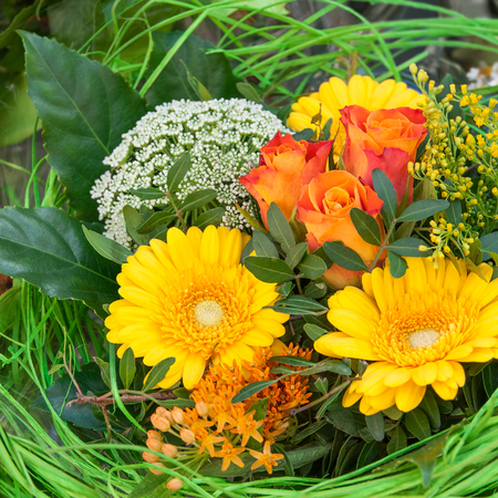 Bunches of sunflowers and roses wrapped in cellophane offer stock 48756497 vibrant flower bouquet with yellow gerbera and orange roses decorated with green grass easter nest floral easter greetings mightylinksfo