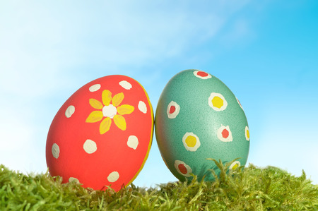 Two hand painted Easter eggs on green moss against blue sky