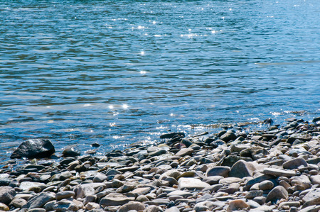 Shimmering surface with pebbled river riverbank; Sunny day on the Rhine