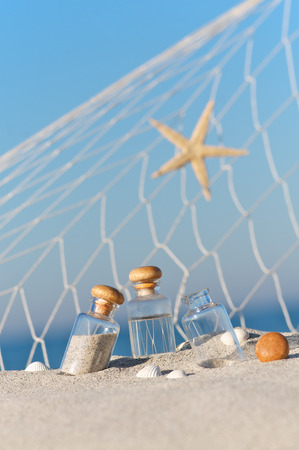 seawater: Small glass bottles with sand and seawater, sea star, shells and fishing net Arranged on Sandy Beach; Holiday souvenirs