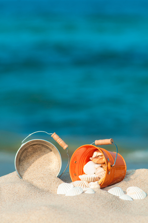 Two metal buckets filled with sand and sea shells on the beach against blue ocean; Relaxing holiday Activity Stock Photo