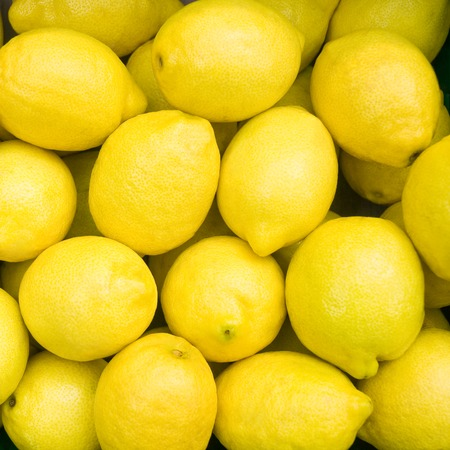 importation: Bright yellow lemons in close up