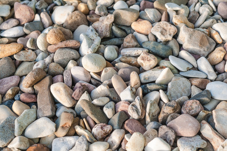 Pebble stones in different colors and sizes in top view for background Imagens