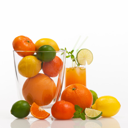 Different citrus fruits and fruit juice against white background; Cocktail ingredients; Vitamin-rich fitness drink Stock Photo
