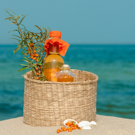 Willow basket with sea buckthorn products in the sand against maritime panorama Stock Photo