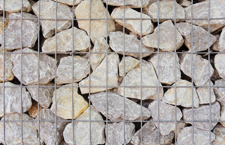 screened: Gabion basket in close up for background or texture; Wire basket filled with rough stones