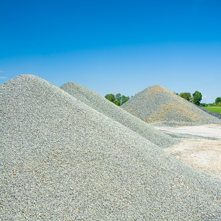 Bright gravel piles against blue sky; Construction materials industry