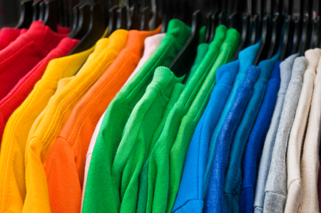 Knit pullovers in rainbow colors Arranged on hangers; Inexpensive mass-produced articles of clothing; Color variety